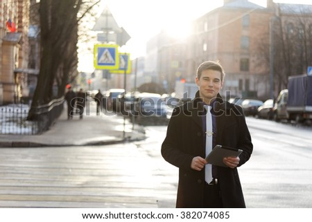 Classic dressed smiling young man with a tablet pc.