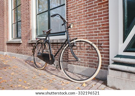 Classic Dutch bicycle parked against a brick wall in autumn, Amsterdam, The Netherlands - stock photo