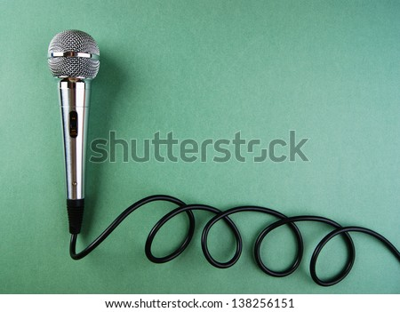 Classic dynamic microphone on a green background - stock photo