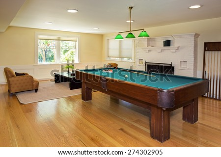 Classic Entertainment Room with white fire place, wooden floor and pool billiard in luxury home. Huge billiard room with massive fireplace and built-in cabinet - stock photo