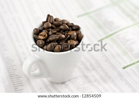 Classic espresso cup on financial pages, shallow depth of field - stock photo