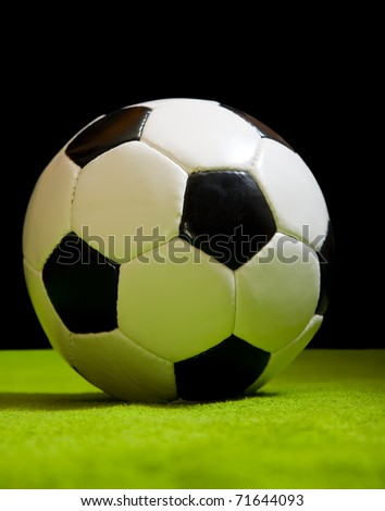 classic football ball on green over black - stock photo