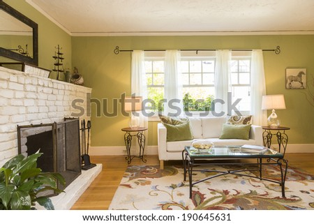 Classic green and white living room interior with hardwood floor and fitted fire place. - stock photo