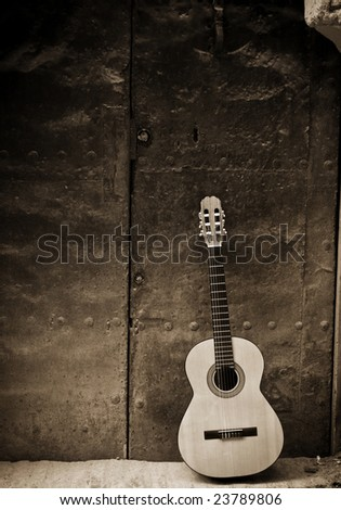 Classic guitar on old door, sepia toned. - stock photo