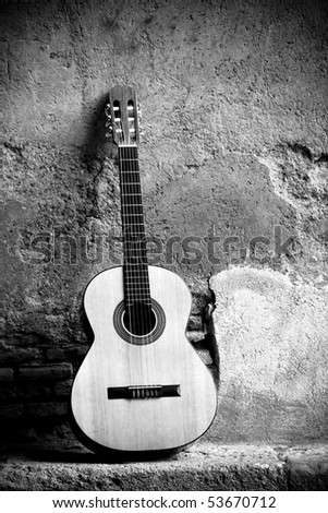 Classic guitar on wall, sepia toned. - stock photo