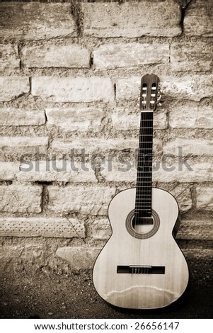 Classic guitar over old brickwall - stock photo