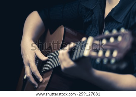 Classic guitar - Vintage toned image of musician hands playing an acoustic guitar - stock photo