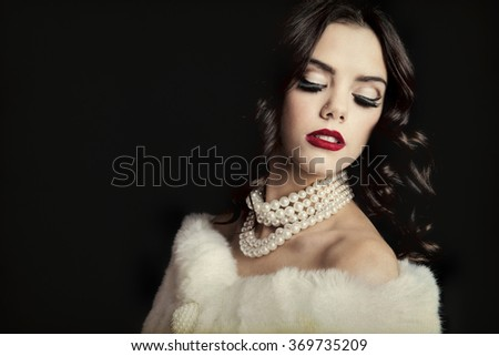 Classic Hollywood starlet in white fur stole, classic pearl necklace, and bright red lipstick.  Shot on black background.