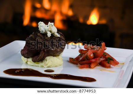 Classic 3 inch center cut filet mignon fire-grilled to perfection sitting on top of mashed potatos adorned with bleu cheese. - stock photo