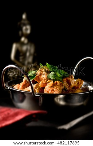 Classic Indian buttered chicken with roasted coriander, tomatoes and honey with a rich marinade coconut sauce set against a dark Indian styled background. Copy space.
