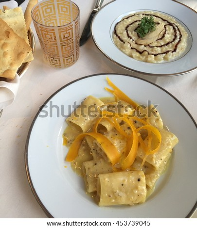 Classic italian first course dishes. Closer dish: paccheri pasta in cheese and pepper sauce  with orange's skin. Far-off dish: risotto (italian rice) with cheese and balsamic vinegar