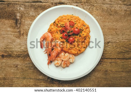 classic italian risotto with shrimps and prawns on a wooden background