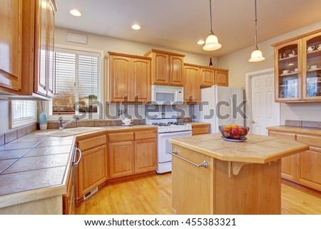 Classic kitchen room interior with brown cabinets, island and hardwood floor
