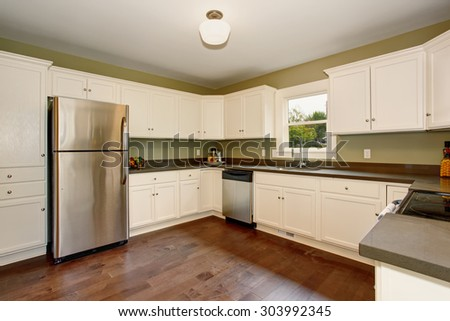 Classic kitchen with green interior paint, hardwood floor, and white cabinets. - stock photo