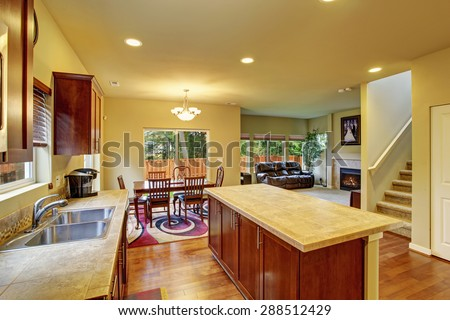 Classic kitchen with hardwood floor, island, and connected dinning room, and living room.
