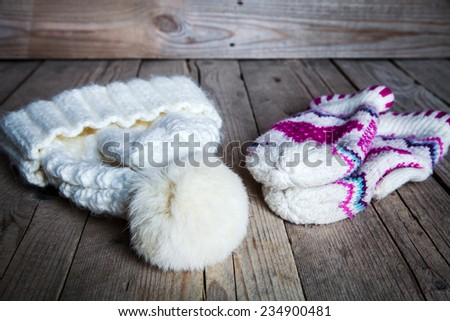 Classic knitted set of mittens and hats on the old wooden background - stock photo