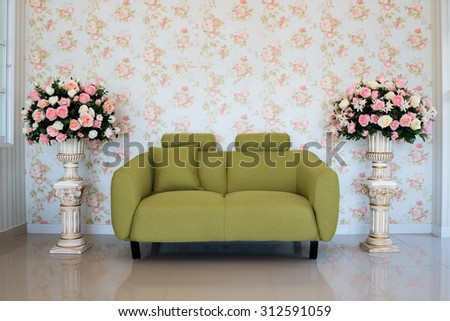 Classic living-room interior with green couch and flower