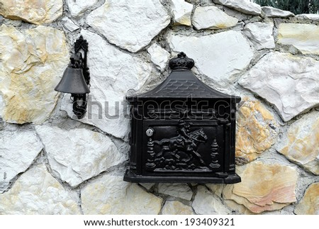 Classic mailbox and Vintage doorbell on a house stone wall - stock photo