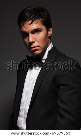 Classic male portrait of handsome mature adult in suit on dark background - stock photo