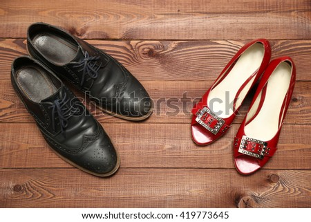 Classic man shoes and red woman sandals on brown wooden background - stock photo