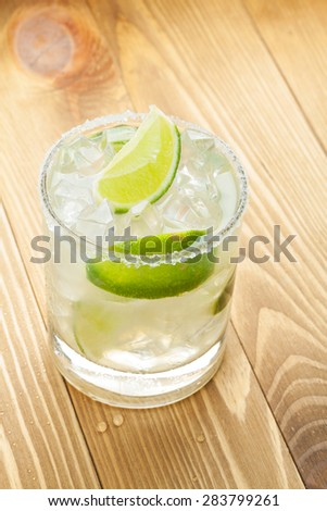 Classic margarita cocktail with salty rim on wooden table - stock photo