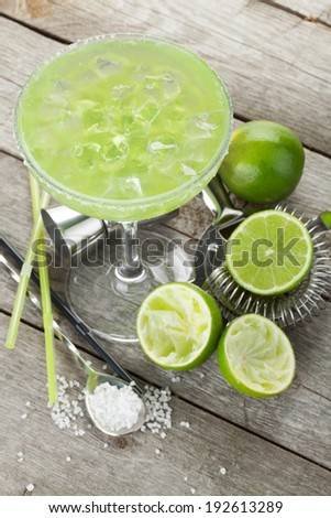 Classic margarita cocktail with salty rim on wooden table with limes and drink utensils - stock photo