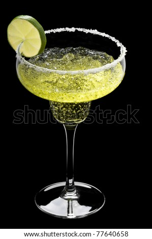 Classic Margarita in front of a black background with fresh garnish - stock photo