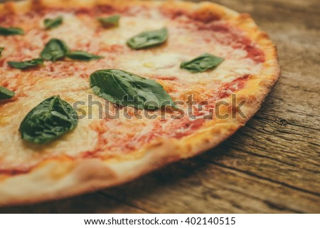classic margherita pizza with tomatoes, basil and mozzarella cheese on a wood background