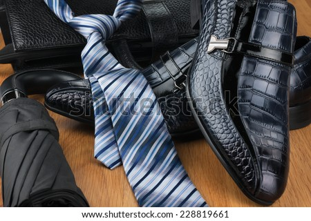 Classic men's shoes, tie, umbrella and bag on the wooden floor, can be used as background - stock photo