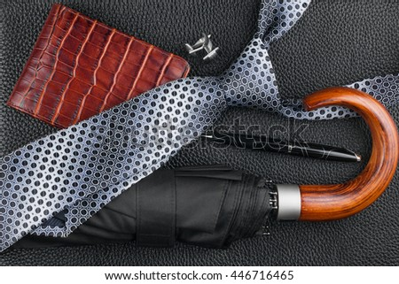 Classic mens accessories, tie, umbrella, purse, pen, cufflinks on natural leather, can be used as background - stock photo