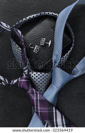 Classic mens  necktie, wallet, cufflinks  lying on the skin, can be used as background