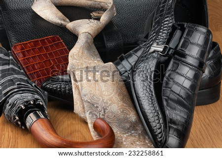 Classic mens shoes, tie, umbrella,wallet  and bag on the wooden floor, can be used as background - stock photo