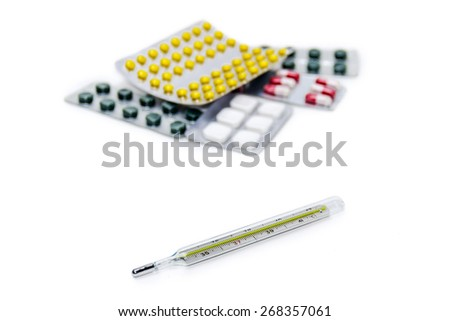 Classic mercury medical thermometer on the  blurred background of the different packages with medicines. Isolation.  - stock photo