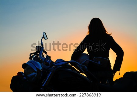 classic motorcycle and girl silhouette at dusk - stock photo