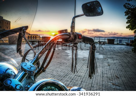 classic motorcycle by the sea at sunset in hdr tone mapping effect - stock photo
