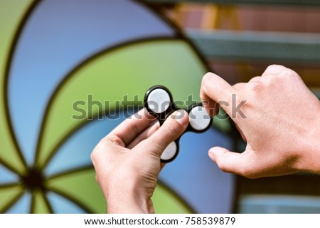 Classic new trendy game for all. Hand spinner fidgeting hand toy. On background of picture symbolize dynamics of, symbol of movement, character dynamics, come on come on, dynamic game