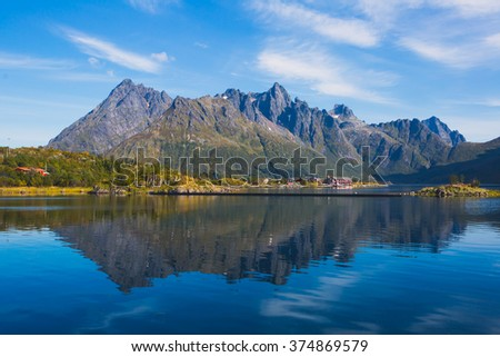 Classic norwegian scandinavian summer landscape with mountains, fjord, lake and a church, with a blue sky, Norway, Lofoten Islands