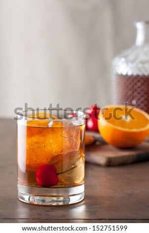 Classic old-fashioned cocktail with a cherry on a wooden table - stock photo