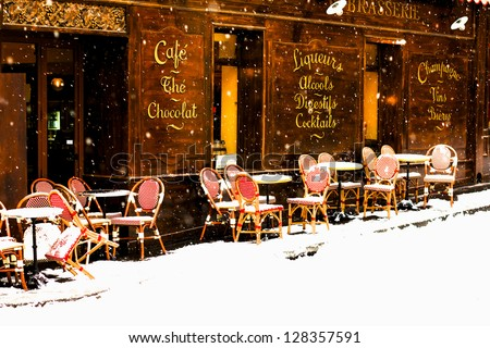 Classic old street brasserie in Paris viewed under the snowfall. Terrace circular tables and woven chairs are covered with fresh snow / Parisian caf�© under the snowfall - stock photo