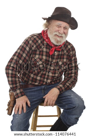 Classic Old West style cheerful cowboy has felt hat, grey whiskers, revolver. Seated on stool. Isolated on white, vertical, copy space. - stock photo