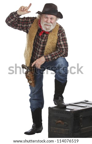 Classic old west style cowboy points up. He has felt hat, grey whiskers, revolver, and stands with one foot up on a wooden chest. Isolated on white, vertical, copy space. - stock photo
