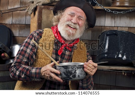 Classic Old West style cowboy with felt hat, grey whiskers, red bandana. He holds a saucepan. Camp cookware and wood shingles in background. - stock photo