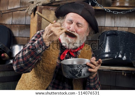 Classic Old West style cowboy with felt hat, grey whiskers, red bandanna. He closes eyes and savors food in a saucepan. Camp cookware and wood shingles in background. - stock photo