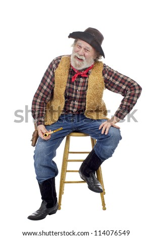 Classic Old West style smiling cowboy with felt hat, grey whiskers, revolver. He sits on stool holding a corn cob pipe. Isolated on white, vertical, copy space. - stock photo