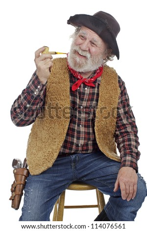 Classic Old West style smiling cowboy with felt hat, grey whiskers, revolver, holds corn cob pipe and sits on stool. Isolated on white, vertical, copy space. - stock photo