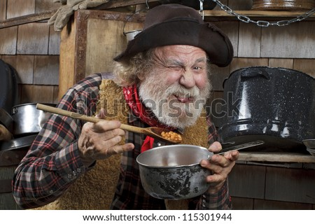 Classic old western style cowboy with felt hat, grey whiskers, red bandanna. He eats beans from a saucepan. Camp cookware and wood shingles in background.