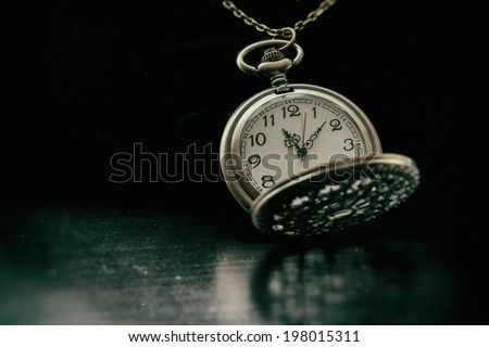 Classic Pocket Watch. An old fashioned looking pocket watch timepiece. shot on black and edited in vintage film style. - stock photo