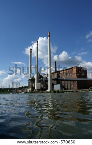 Classic power plant reflecting in river with blue sky background
