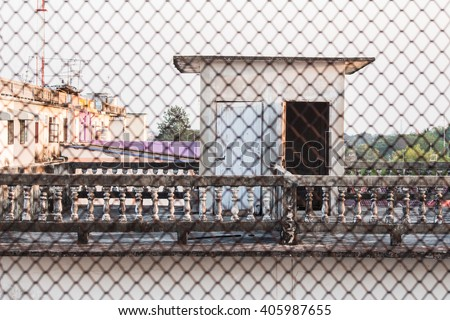 Classic railing design on the roof and blur of metal fence grid. - stock photo
