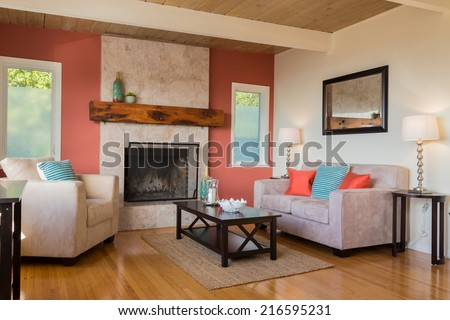 Classic red and white living room interior with hardwood floor. Fitted fire place and red, blue pillows on sofa, couch with hand-woven natural colored fine sisal runner, rug.  - stock photo